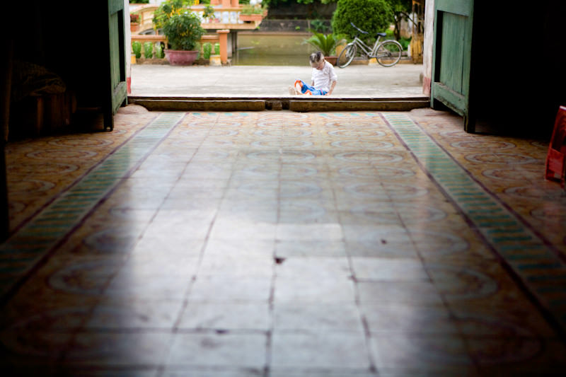 A child with a rare fish scale disease sits alone outside the local church. - Thai Binh, Vietnam - SEND ME - Donor Awareness