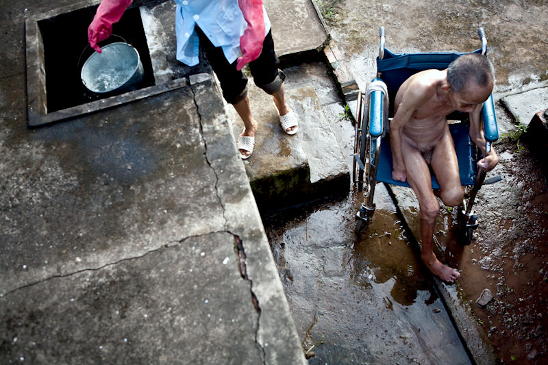 An elderly man is given a shower at the Van Mon Leprosy village. - Thai Binh, Vietnam - SEND ME - Donor Awareness