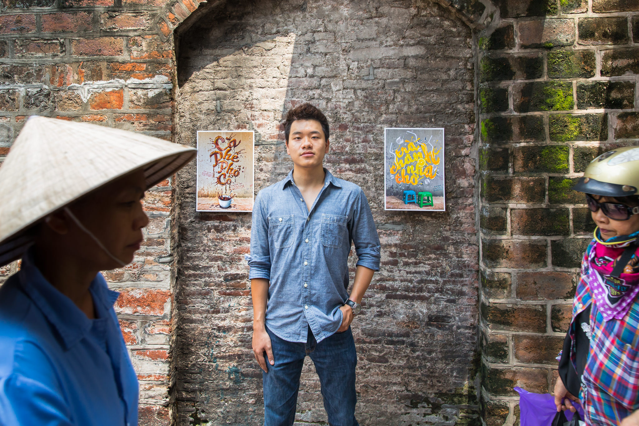 Hanoian Dao Duy Duong stands in front of his graphic design and typography work which is hanging under Hanoi's busy old city gate in Hoan Kiem, Hanoi, Viet Nam | Hanoi Photographer