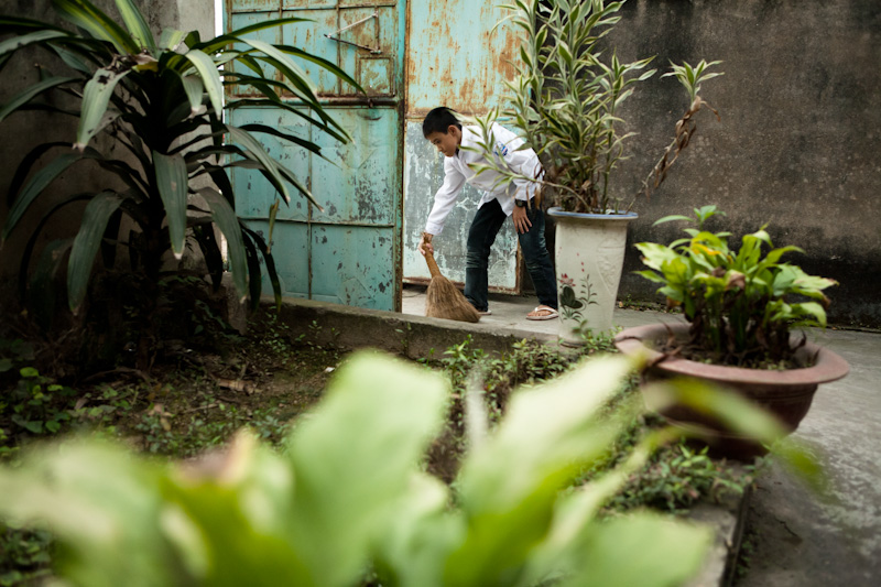 Ninh sweeps the front of his house every morning before he goes to school. Since his father passed away Ninh tries to help his mother as much as he can.