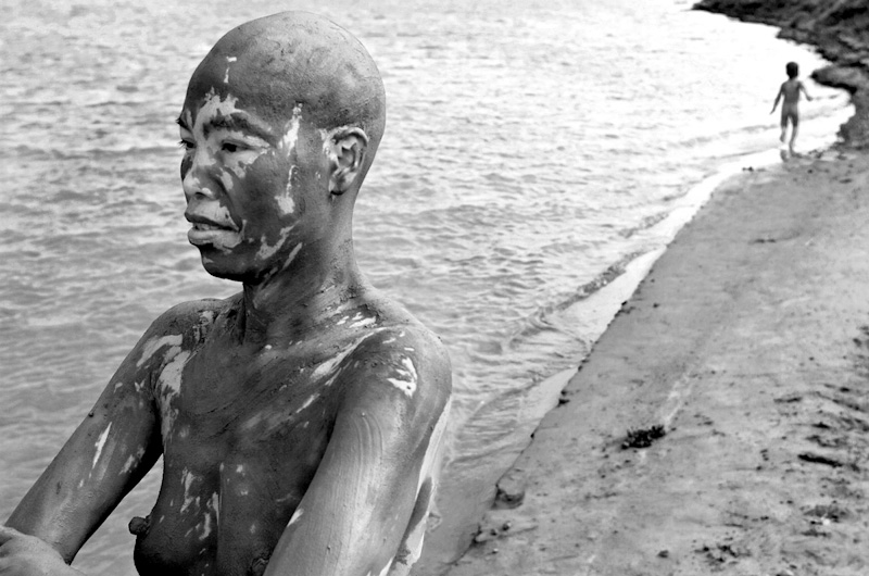 During a mud was pha runs down the beach on the Red River as Mui stares off into the distance as she cleans herself.