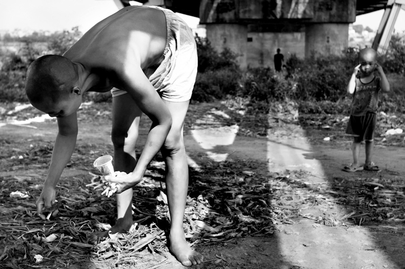 Mui, bends down to pick up heroin needles, as her son Pha, stands next to her. They live in an area known throughout the city for its high rate of crime and heroin use. The day after the celebration of Tet, the Vietnamese New Year, there was a large amount of heroin needles around where they walk every day under the Long Bien Bridge. Mui spent an hour picking upwards of a hundred needles barefoot and placing them in one pile out of harm's way. Everywhere Mui walks, she habitually picks up the garbage around her and thinks by doing so she is making the world around her a better place.
