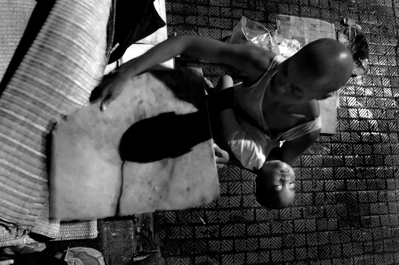 Every night, Mui, and her son, Pha, sleep in the street close to the Long Bien Train Station. While her son sleeps, Mui stays up late to clean up the newspaper she uses as a place setting for their dinner. Mui always carries her son to their sleeping area and covers him in a blanket before she finishes with her chores.