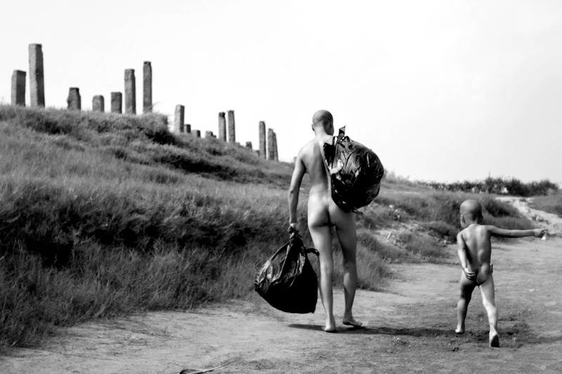Mui carries all the valuable possessions she owns in the two garbage bags as she walks ahead of her son while he runs to catch up with her. Every day they walk the same route to their spot on the Red River where they spend hours playing on the beach.