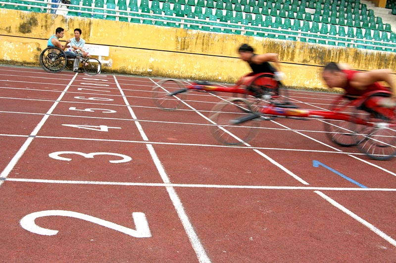 The coach of the wheelchair racing team talks to one of his athletes during practice.