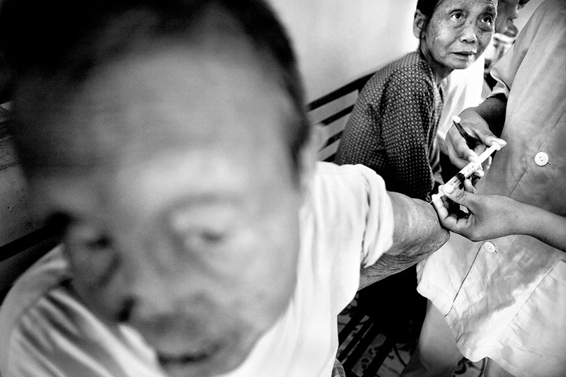 Bop receives an injection from a nurse as Mai watches her cautiously. The nursing care at the Van Mon Village and hospital is often brash and lacks basic empathy for these patients.