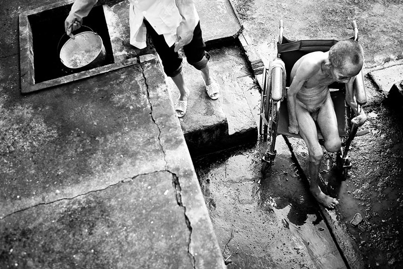 Binh, waits for his next bucket from his cold-water bath. This is the common way the nursing staff wash their patients. First they put them into a wheelchair, nude, and then bring them outside and throw buckets of water on them. The nurses wash their patients every Tuesday and Friday morning. They have no hot water for these kinds of baths in the winter due to a lack of funding