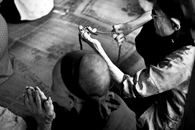 Nguyen My Linh holds her prayer beads as she prays in the Village's Buddhist temple.